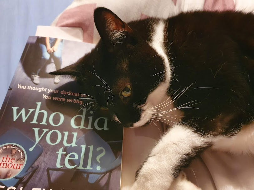 The book Who Did You Tell? being used as a pillow by a black and white cat